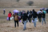 "Soldiers are seen among migrants walking towards the forest after camp ""Lipa"" was closed, in Bihac"