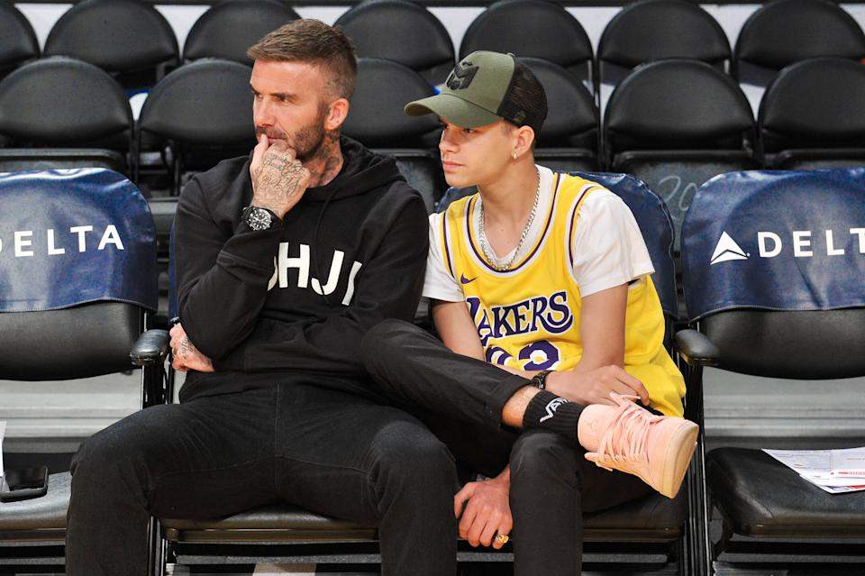 LOS ANGELES, CALIFORNIA - OCTOBER 27: David Beckham (L) and his son Romeo Beckham attend a basketball game between the Los Angeles Lakers and the Charlotte Hornets at Staples Center on October 27, 2019 in Los Angeles, California. (Photo by Allen Berezovsky/Getty Images)