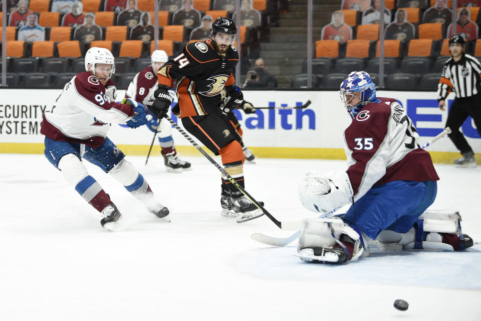 Colorado Avalanche left wing Gabriel Landeskog, left, and Anaheim Ducks center Adam Henrique (14) battle for position as the puck deflects off a save by Avalanche goalie Jonas Johansson during the second period of an NHL hockey game in Anaheim, Calif., Friday, April 9, 2021. (AP Photo/Kelvin Kuo)