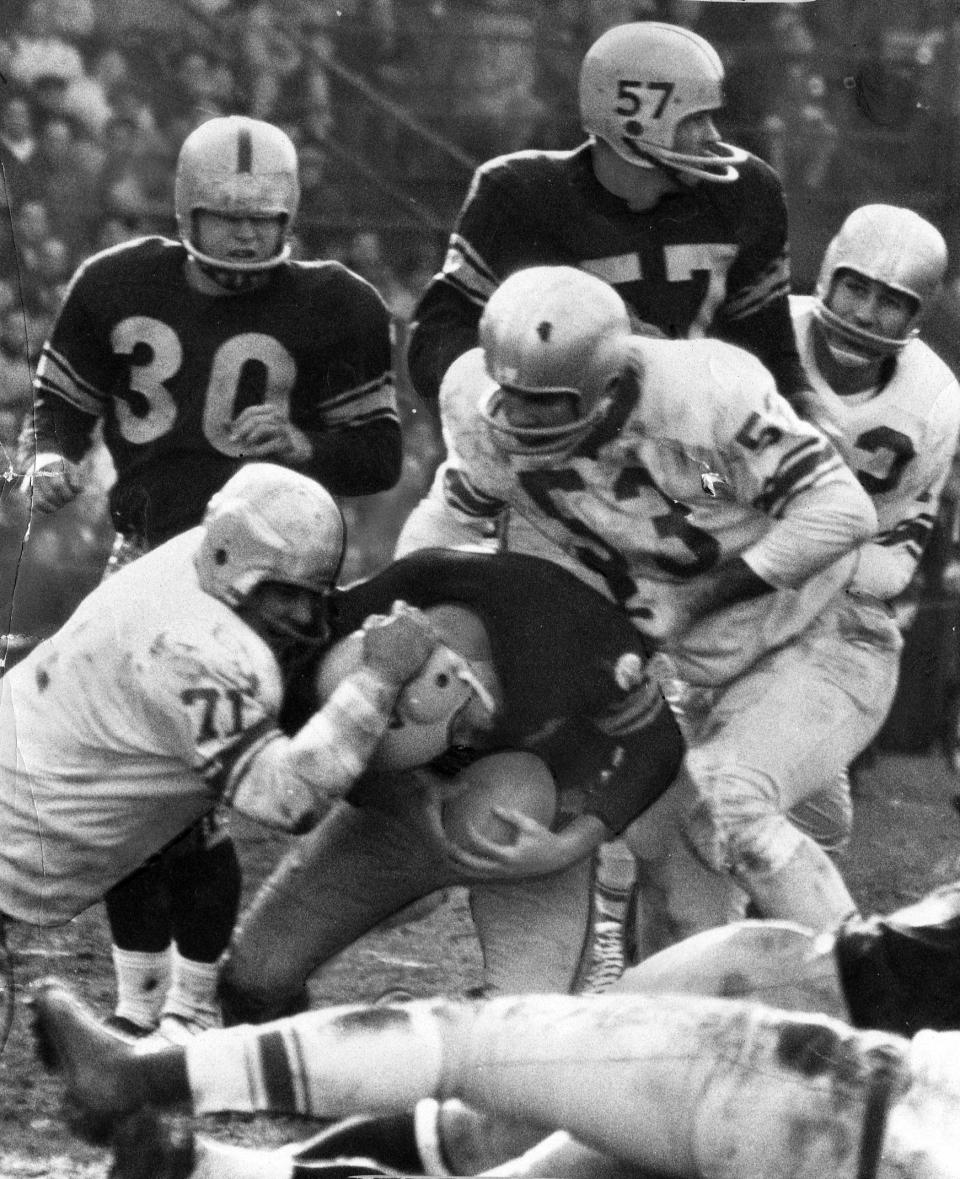 """FILE- Detroit Lions defensive tackle Alex Karras (71) helps with the tackle of an unidentified Pittsburgh Steelers football player in Pittsburgh, in this Nov. 8, 1959, file photo. A dozen seasons as one of the most feared pass-rushers in the NFL turned out to be just an opening act for Alex Karras. The Lions' four-time Pro Bowl star was a natural in front of the camera, whether crumpling quarterbacks, needling then-commissioner Pete Rozelle or sharing stories with Johnny Carson on """"The Tonight Show."""" Karras used that tough-guy image to launch a second career as a sportscaster, and a sitcom and movie star. (The Detroit News via AP)"""