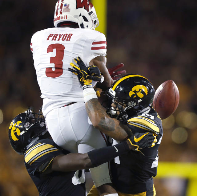 Iowa defensive backs Matt Hankins, left, and Amani Hooker, right, dislodge the ball from Wisconsin wide receiver Kendric Pryor, center, resulting in an incomplete pass during the first half of an NCAA college football game Saturday, Sept. 22, 2018, in Iowa City. (AP Photo/Matthew Putney)