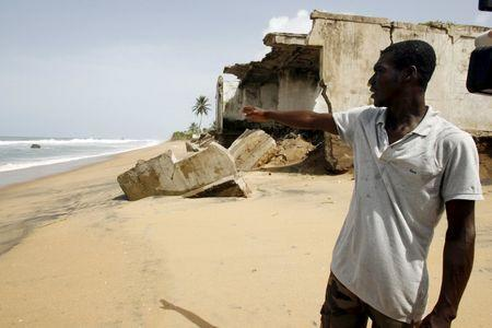 A resident talks near abandoned houses damaged by erosion on a beach in Grand-Lahou on the southern Ivory Coast, in this June 8, 2010 file photo. REUTERS/Luc Gnago