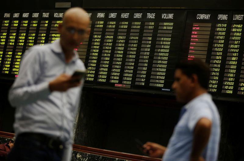 Men use their cell phones as they stand in front of electronic board displaying share market prices in the halls of Pakistan Stock Exchange in Karachi