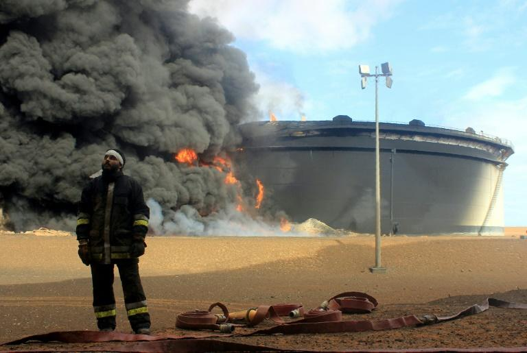 A Libyan fireman stands in front of smoke and flames rising from an oil storage tank in northern Libya's Ras Lanouf region on January 23, 2016, after it was set ablaze earlier in the week following attacks launched by the Islamic State group