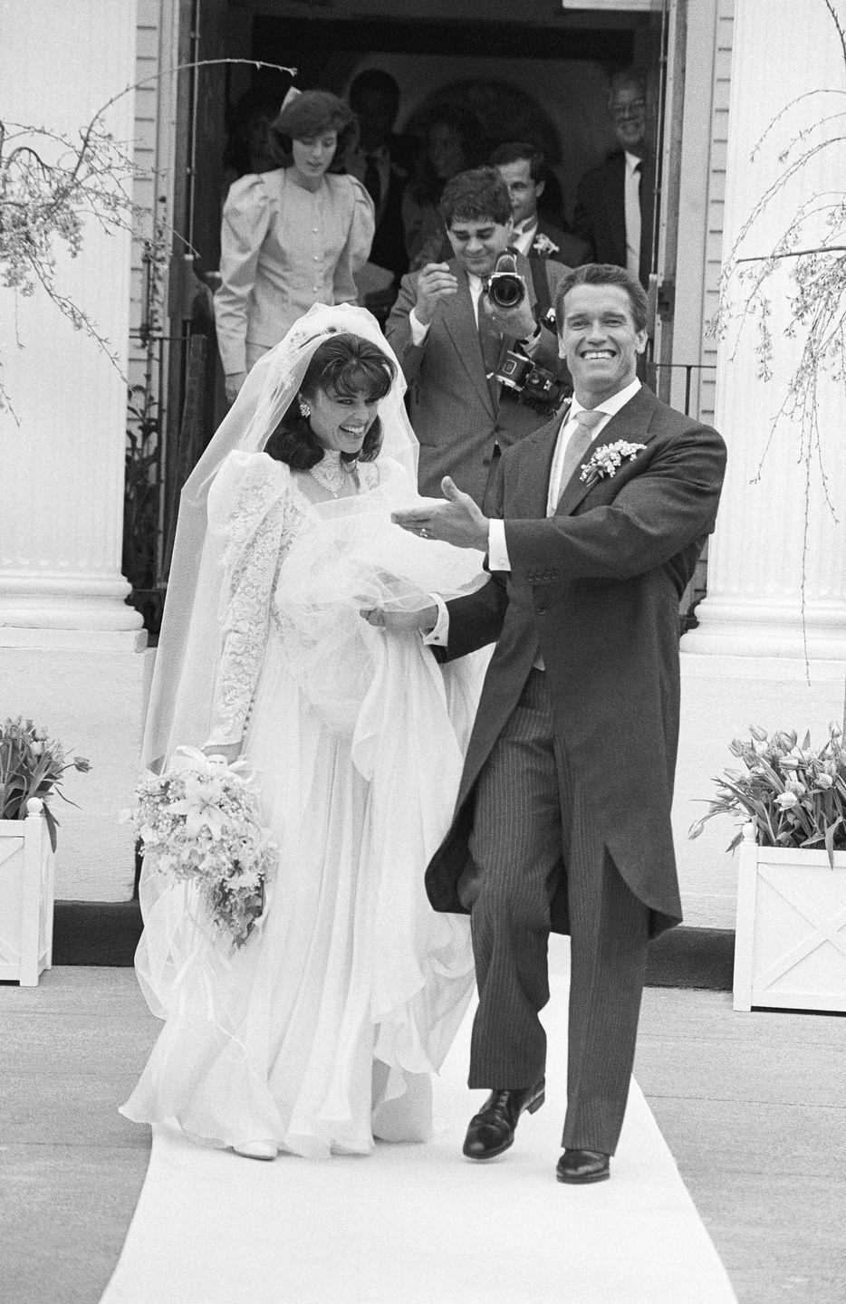 <p>Beaming with pride, Arnold Schwarzenegger helps his new wife, Maria Shriver, with her veil as the two depart the St. Francis Xavier Church in Hyannis, Massachusetts. </p>