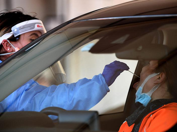 A health worker takes a swab sample at a Covid-19 drive-through testing site in western Sydney on August 7, 2021