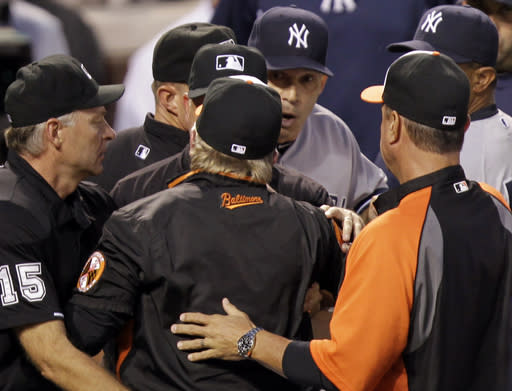 Baltimore Orioles manager Buck Showalter, center back to camera, argues with New York Yankees manager Joe Girardi, center right, at the end of the first inning of a baseball game between their teams, Monday, Sept. 9 2013, in Baltimore. (AP Photo/Luis M. Alvarez)