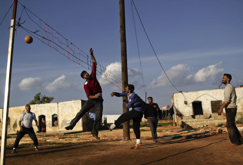 In this Friday, Dec. 14, 2012, photo, Syrian men, who fled their homes with their families due to government airstrikes and took refuge in a school, play volleyball in a field in Maaret Misreen, near Idlib, Syria. The town is broke, relying on a slowing trickle of local donations. The rebels, a motley crew of laborers, mechanics and shopowners, have little experience in government. President Bashar Assad's troops still control the city of Idlib a few miles away, making area roads unsafe and keeping Maaret Misreen cut off from most of Syria. (AP Photo/Muhammed Muheisen)