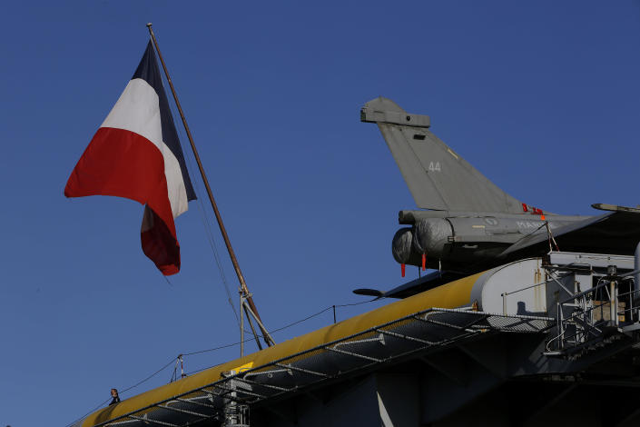 """A French crew member stands next of a French flag and an aircraft on the France's nuclear-powered aircraft carrier Charles de Gaulle at Limassol port, Cyprus, Monday, May 10, 2021. With the Task Force's deployment on its mission named """"Clemenceau 21,"""" France is assisting in the fight against terrorism while projecting its military power in regions where it has vital interests. (AP Photo/Petros Karadjias)"""