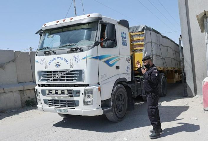 A Palestinian policeman ushers in a truck carrying goods through the Kerem Shalom crossing in Rafah, in the southern Gaza Strip, the main passage point for goods entering the enclave from Israel