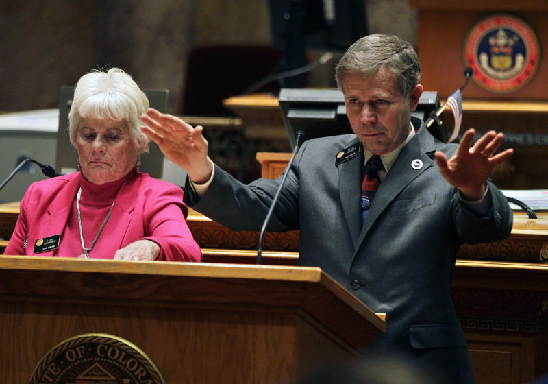 Colorado Sen. Lois Tochtrop, left, listens as Sen. Kevin Lundberg, right, speaks at the podium during a debate period on a day of voting on gun control bills before the Colorado Legislature, at the State Capitol, in Denver, Friday March 8, 2013. Colorado Democrats are on the cusp of advancing gun-control proposals Friday in a state balancing a history of heartbreaking shootings with a Western heritage where gun ownership is treasured by many. (AP Photo/Brennan Linsley)