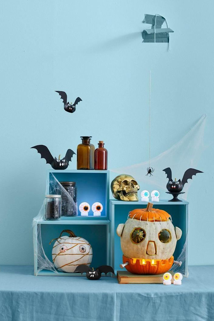 <p>Paint any mini pumpkin black, use white-painted pumpkin seeds for teeth and cut ears and wings out of cardstock. Glue googly eyes on top of eye-shaped paper cutouts to finish of these spooky gourds.</p>