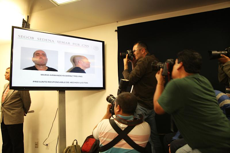Reporters take videos and photos of mug shots showed on a TV screen of the top leader of Mexico's Gulf Cartel Mario Armando Ramirez Trevino during a news conference given by the Mexican government in Mexico City, Sunday, Aug. 18, 2013. Mario Armando Ramirez Trevino, a top leader of Mexico's Gulf Cartel, was detained on Saturday Aug. 17 in a military operation near the Texas border, just weeks after the arrest of the leader of the brutal Zetas cartel near another border city, Nuevo Laredo. (AP Photo/Marco Ugarte)
