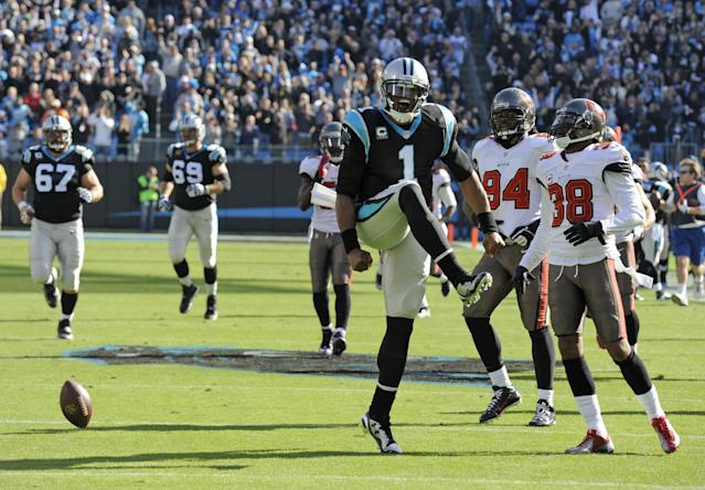 Carolina Panthers quarterback Cam Newton (1) celebrates after running for a long gain against the Tampa Bay Buccaneers in the first half of an NFL football game in Charlotte, N.C., Sunday, Dec. 1, 2013. (AP Photo/Mike McCarn)