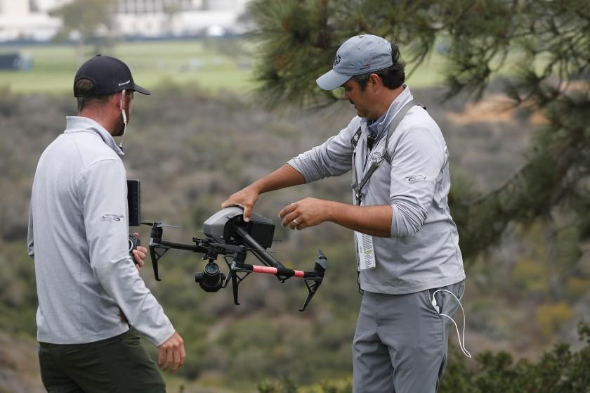 SAN DIEGO, CA - JUNE 16: Drone operator Ben McClung picks up a drone used for coverage of the U.S. Open at the Torrey Pines golf course on Wednesday, June 16, 2021 in San Diego, CA. Tanner Deprin, left, looks on. (K.C. Alfred / The San Diego Union-Tribune)