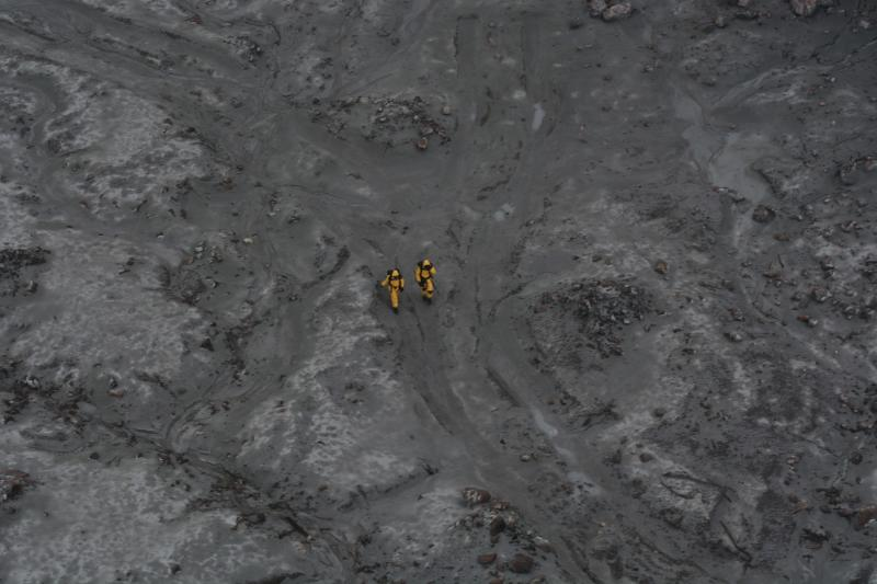 Two people in yellow jumpsuits are seen walking across ash-covered White Island.