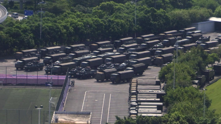 In this image made from video, armed police vehicles are parked outside Shenzhen Bay Stadium in Shenzhen, near Hong Kong, Friday, Aug. 16, 2019.(AP Photo/Dake Kang)