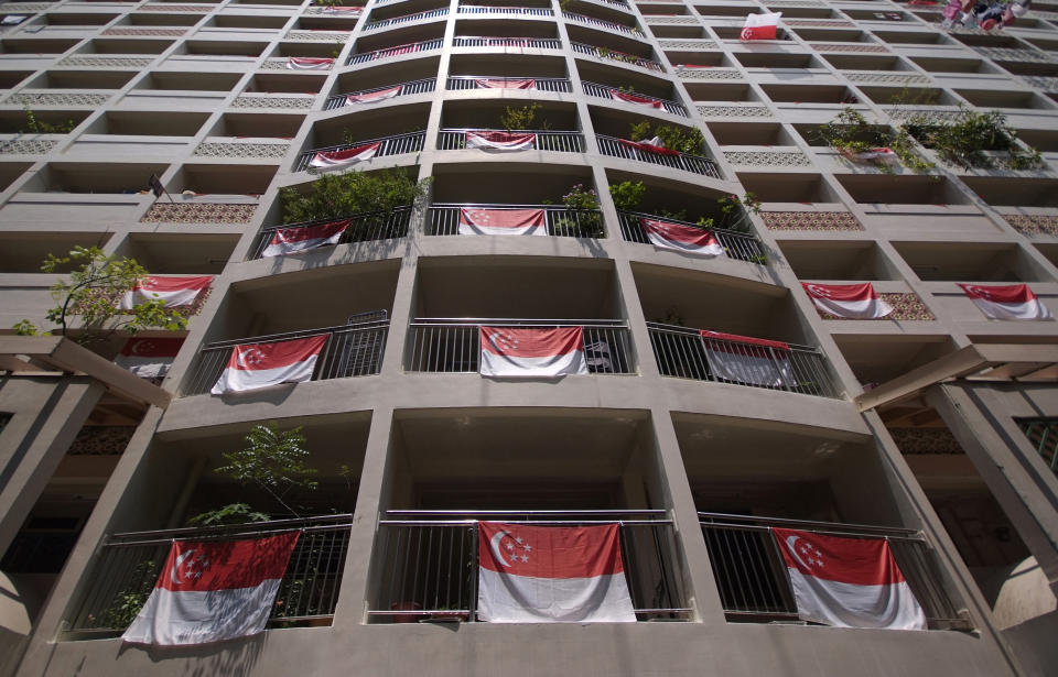 Singapore's national flags are displayed from an apartment block during National Day in central Singapore August 9, 2011. Singapore celebrates its 46th National Day on Tuesday, with its economy likely to expand by five to six percent this year, Prime Minister Lee Hsien Loong said on August 8, 2011, indicating the government now expects growth to come in at the lower end of its five to seven percent forecast.   REUTERS/Kevin Lam (SINGAPORE - Tags: SOCIETY ANNIVERSARY)
