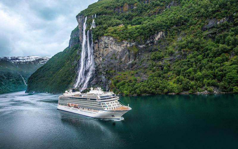 A Viking ocean ship sails by the Seven Sisters waterfall in Geirangerfjord - Viking Cruises owns all rights to images for unlimited time and usage/media, worldwide, for all images. Photographer retains right to use images for self-promo on own website, but may not refer to