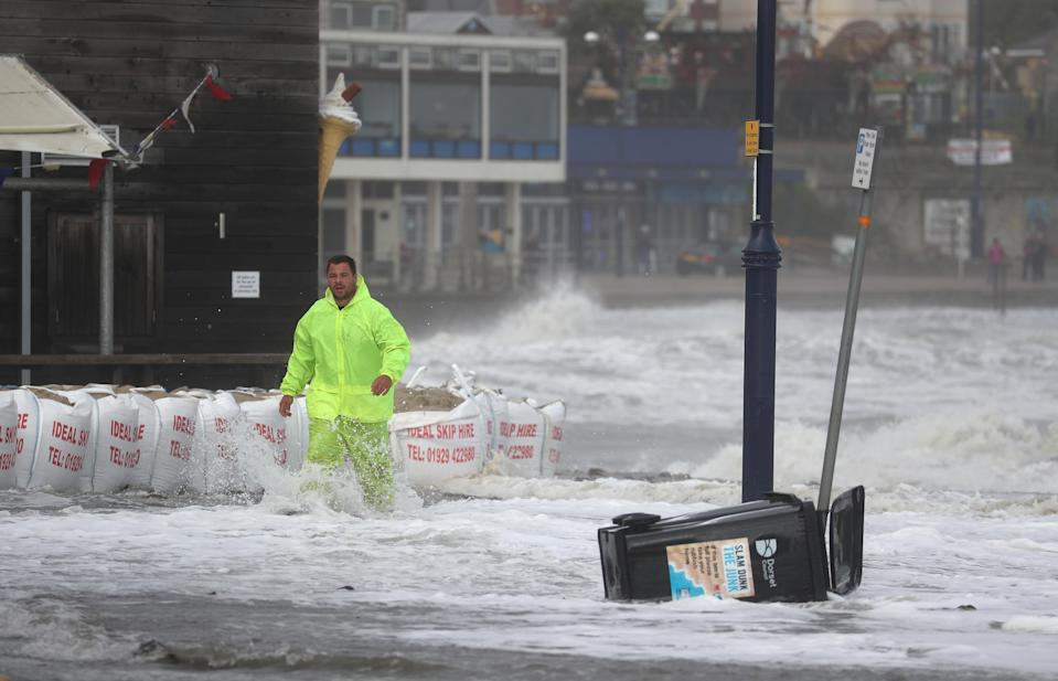A man walks through waves as they crash along the coast at Swanage in Dorset. Parts of the UK are preparing to be lashed by heavy rain and high winds as Storm Alex heralds the arrival of a stretch of bad weather over the weekend.