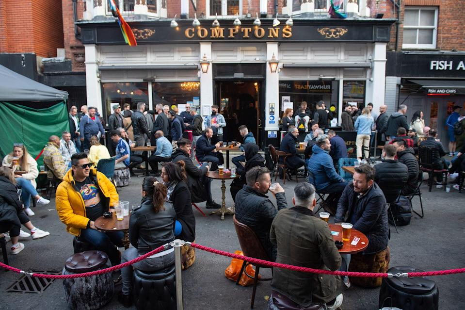 <p>People eat and drink at outside tables in Soho</p> (PA)
