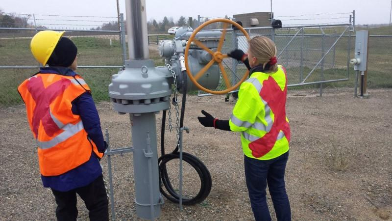 Activists are seen attempting to shutdown oil pipeline valve after cutting chains at a valve station for pipelines carrying crude from Canadian oils sands into the U.S. markets near Clearbrook