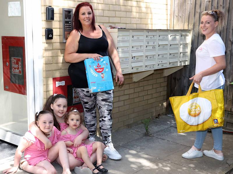 Becca Archer with her three daughters, given food donation by volunteer Katie-Louise Barber: Nigel Howard