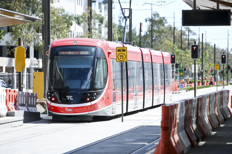 A new Canberra light rail tram is seen travelling along on its track.