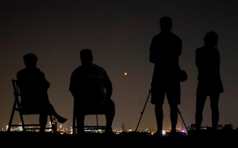 People in a field watch the moon over the skyline of Frankfurt, Germany. (Kai Pfaffenbach / Reuters)