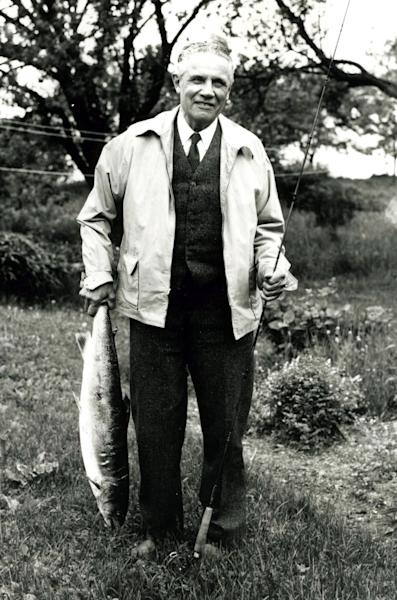 FILE - In this 1945 file photo provided by the L.L. Bean Archive, Leon Leonwood Bean holds a 19-pound salmon in Plaster Rock, New Brunswick, Canada. As outdoors outfitter L.L. Bean celebrates its 100th anniversary, it's still not 100 percent clear what the famous founder's initials stood for. It could be Leon Leonwood Bean, as the company claimed for decades, or was it Leon Linwood Bean, as his grandson suggest. (AP Photo/The L.L. Bean Archive, File)