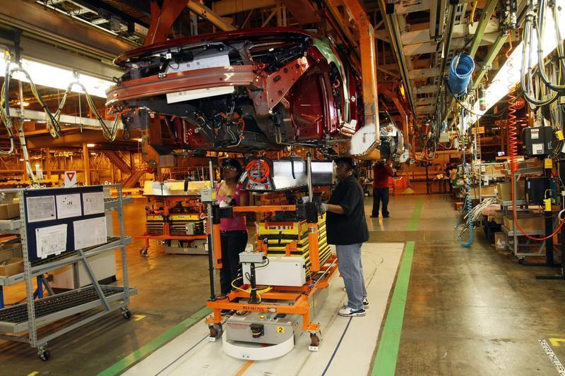 General Motors assembly workers Monique Watson (L) and Evetta Osborne install an electric battery on the underside of a 2011 Chevrolet Volt electric vehicle at the Detroit-Hamtramck Assembly plant in Hamtramck, Michigan
