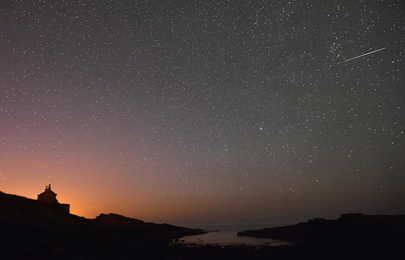 A star-filled night as a meteor is snapped streaking across the sky.