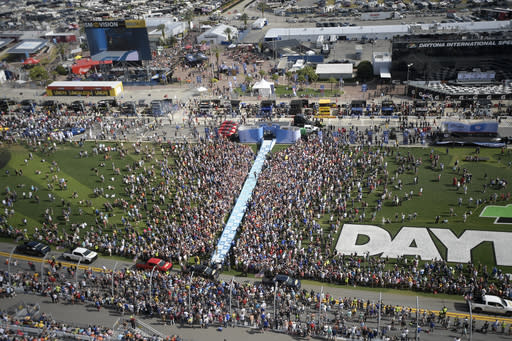 FILE - Fans watch as drivers walk down a runway during driver introductions before the NASCAR Daytona 500 auto race at Daytona International Speedway Sunday, Feb. 17, 2019, in Daytona Beach, Fla. The party has been canceled during the pandemic but the playoffs go on, starting Sunday, Sept. 6, 2020, without any of the pomp and circumstance.(AP Photo/Phelan M. Ebenhack, File)