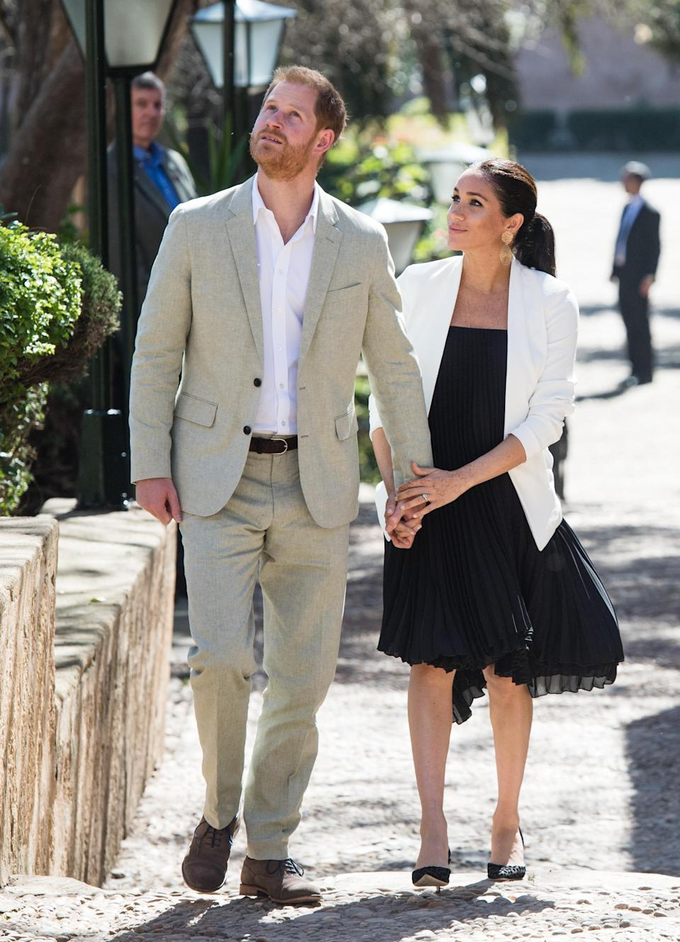 <p>To visit an arts and crafts display in the Andolusian Gardens, the pregnant royal chose a black plisse dress by Loyd/Ford. To accessorise, Meghan also wore her white Babaton 'Keith' Jacket and Manolo Blahnik polka dot slingback pumps. <em>[Photo: Getty]</em> </p>