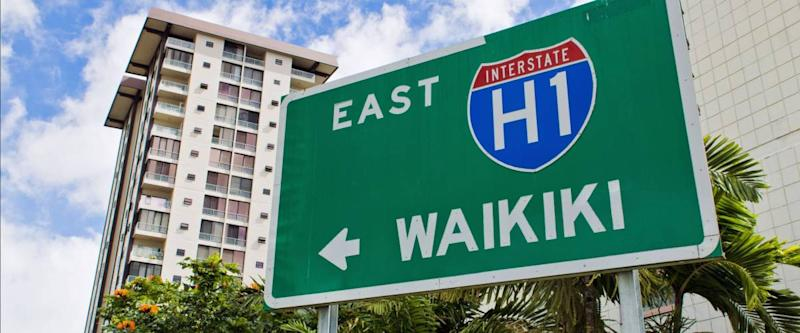 A highway sign points in the direction of Waikiki beach, Oahu, Hawaii.
