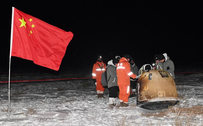 Researchers work around Chang'e-5 lunar return capsule carrying moon samples next to a Chinese national flag, after it landed in northern China's Inner Mongolia Autonomous Region - Reuters