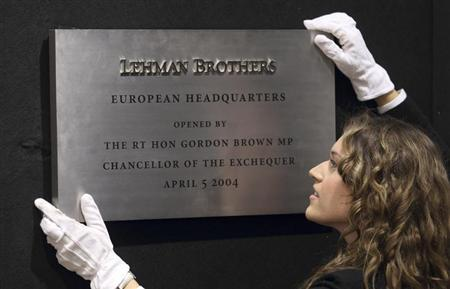 A Christie's employee poses for a photograph with the plaque from Lehman Brothers' European headquarters at Christie's in central London