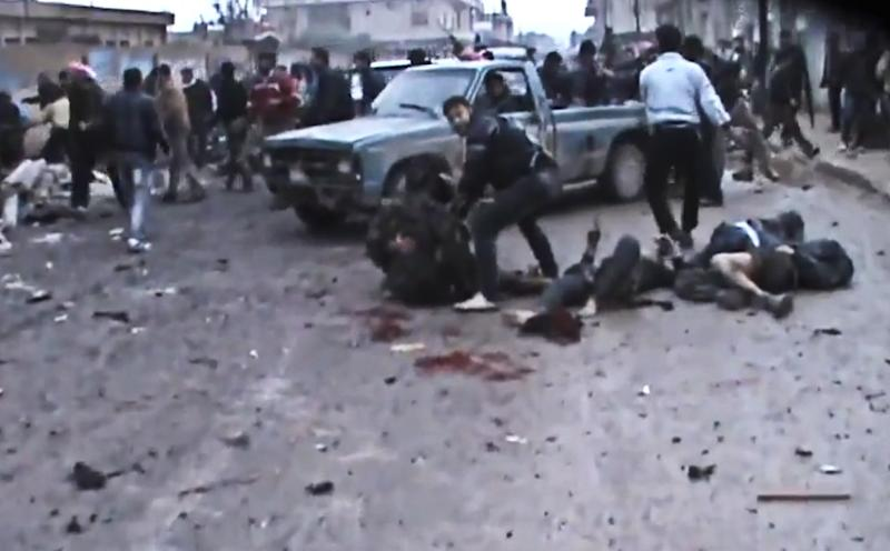 This Sunday, Dec. 23, 2012 image taken from video obtained from the Shaam News Network, which has been authenticated based on its contents and other AP reporting, shows Syrians removing the bodies of those killed after a government airstrike hit the Hama Suburb of Halfaya, Syria. A government airstrike Sunday on a bakery in a rebel-held town in central Syria killed tens of people, which left scattered bodies and debris up and down a street, and more than a dozen wounded were trapped in tangled heap of dirt and rubble, activists said. (AP Photo/Shaam News Network via AP video)