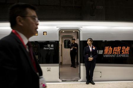 An attendant stands next to an entrance of a Guangzhou-Shenzhen-Hong Kong Express Rail Link (XRL) Vibrant Express train bound for Guangzhou Nan Station on a platform in the Mainland Port Area at West Kowloon Station, which houses the terminal for the XRL, developed by MTR Corp., in Hong Kong, China, September 22, 2018. Giulia Marchi/Pool via REUTERS