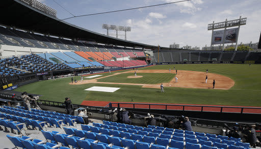 Photographers and TV camera work near empty seats during the pre-season baseball game between Doosan Bears and LG Twins in Seoul, South Korea, Tuesday, April 21, 2020. South Korea's professional baseball league has decided to begin its new season on May 5, initially without fans, following a postponement over the coronavirus. (AP Photo/Lee Jin-man)