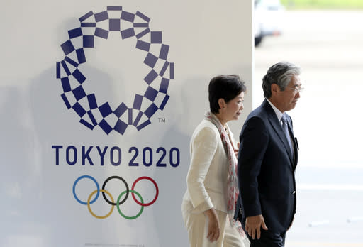 FIEL - In this Aug. 24, 201, file photo, Tokyo Gov. Yuriko Koike, second from right, and Tsunekazu Takeda, president of the Japanese Olympic Committee, walk past the logo of the Tokyo 2020 Olympics during the Olympic flag arrival ceremony at Haneda international airport in Tokyo. The price tag keeps soaring for the 2020 Tokyo Olympics despite local organizers and the International Olympic Committee saying that spending is being cut. (AP Photo/Eugene Hoshiko, File)
