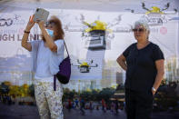 Women look at drones carrying goods as part of the National Drone Initiative test operation and demonstrated for journalists, in Tel Aviv, Israel, Monday, Oct. 11, 2021. This was the third demonstration in Israel of the drone pilot program set to deliver goods and medicine across Israel. (AP Photo/Oded Balilty)