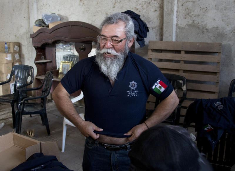 """Vigilante leader Estanislao Beltran puts on an official rural police shirt, before the start of a ceremony in Tepalcatepec, Mexico, Saturday, May 10, 2014. At the ceremony in the town where the vigilante movement began in February 2013, officials handed out new pistols, rifles and uniforms to 120 self-defense group members who were sworn into a new official rural police force. """"Now we are part of the government. Now we can defend ourselves with weapons in a legal way,"""" said Beltran the movement's spokesman, during the ceremony on the grounds of a local rancher's association. (AP Photo/Eduardo Verdugo)"""