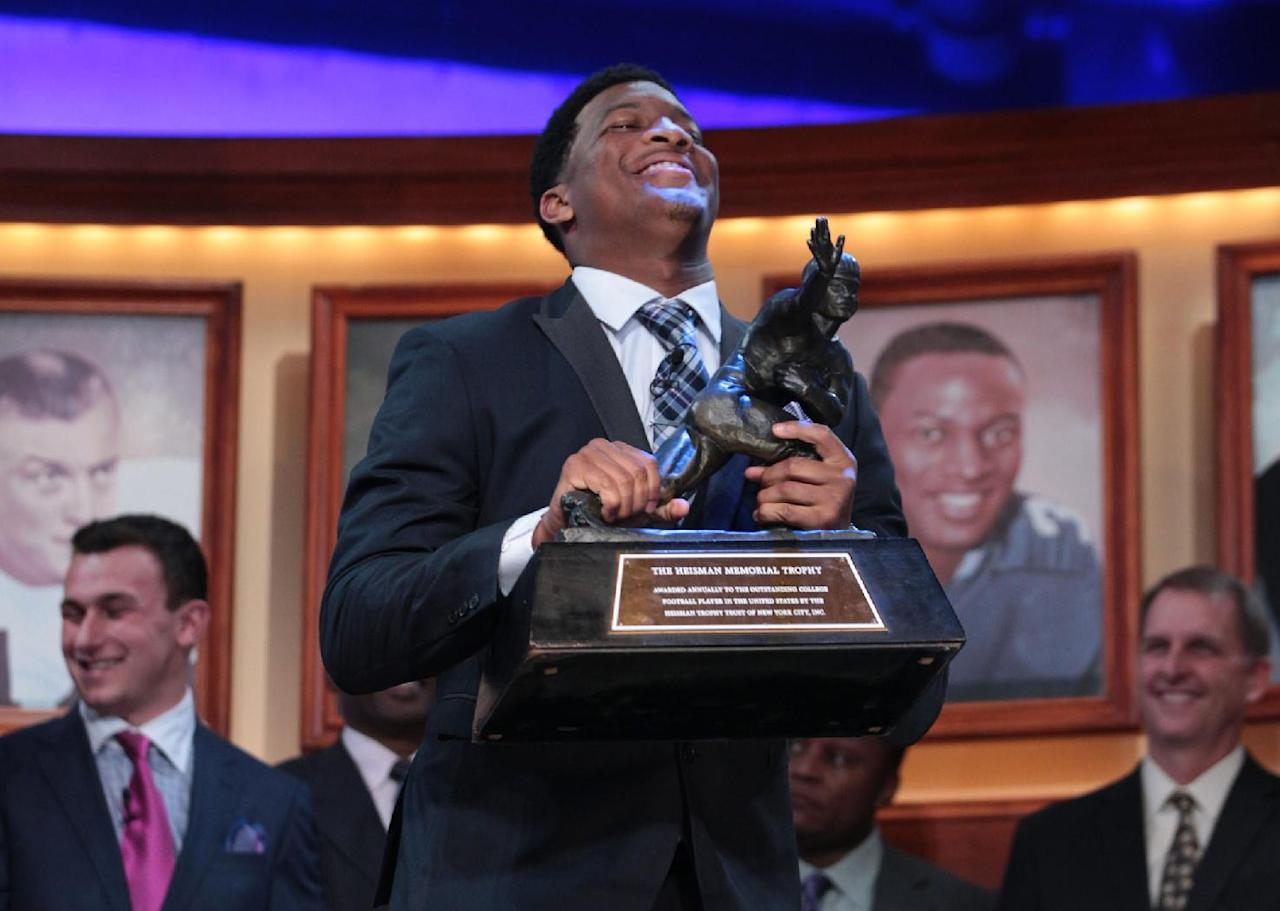 In this photo provided by the Heisman Trust, Florida State quarterback Jameis Winston hoists the Heisman Trophy after being named college football's best player during the Heisman Trophy presentation in New York on Saturday, Dec. 14, 2013. (AP Photo/Heisman Trust, Kelly Kline)