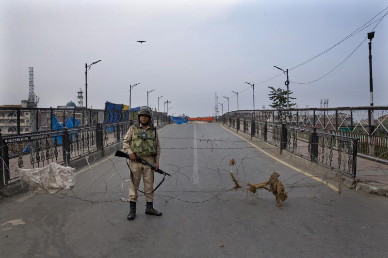 "FILE - In this Friday, Sept. 27, 2019, file photo, an Indian paramilitary force soldier stands guard near a barbwire barricade during restrictions in Srinagar, Indian controlled Kashmir. The Trump administration remains concerned about the ongoing crackdown in India-administered Kashmir, the restive Himalayan region stripped of its special constitutional status in August, but supports India's development ""objectives"" there, Acting Assistant Secretary of State for South and Central Asia Alice Wells said in a statement Tuesday, Oct. 22, ahead of a congressional hearing in Washington. (AP Photo/Dar Yasin, File)"