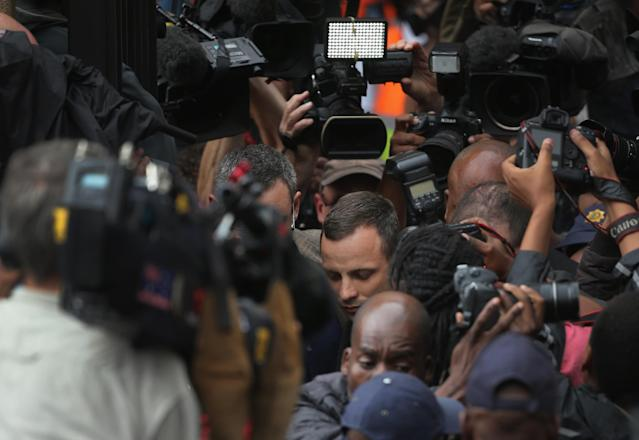 PRETORIA, SOUTH AFRICA - MARCH 04: Oscar Pistorius (C) leaves North Gauteng High Court amid a media scrum after the second day of his trial accused of the murder of his girlfriend Reeva Steenkamp on March 4, 2014 in Pretoria, South Africa. Olympic and Paralympic athlete Oscar Pistorius, aged 27, is accused of murdering his girlfriend Reeva Steenkamp. Pistorius denies the allegation claiming he mistook Steenkamp for an intruder inside their home on Valentine's Day 2013. (Photo by Christopher Furlong/Getty Images)