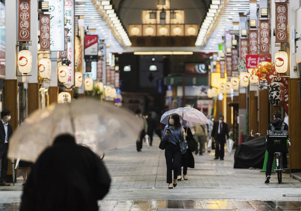 A woman walks through a shopping street in Tokyo on Friday, Oct. 9, 2020. A slow-moving typhoon off Japan's southern coast has triggered gusts and rain across a large part of the country and could bring heavy rains to the Tokyo region through early next week, though it was not expected to make landfall, officials said Friday. (AP Photo/Hiro Komae)