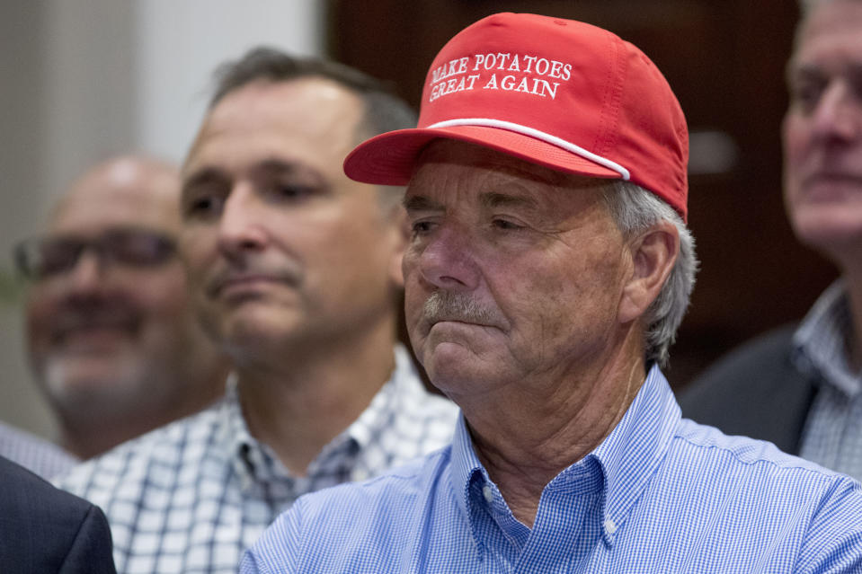 """A guest wears a hat that reads """"Make Potatoes Great Again"""" as President Donald Trump speaks at a meeting to support America's farmers and ranchers in the Roosevelt Room of the White House, Thursday, May 23, 2019, in Washington. (AP Photo/Andrew Harnik)"""