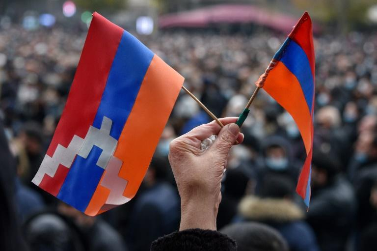 A woman holds a flag (L) of the breakaway Nagorno-Karabakh region and an Armenian flag (R) during a rally against a controversial peace agreement with Azerbaijan in Yerevan on December 5, 2020 (AFP/Karen MINASYAN)