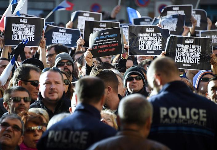 Policemen look on as people hold signs during a unity rally on January 11, 2015 in Beaucaire (AFP Photo/Pascal Guyot)